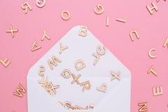 Enveloppe blanche ouverte avec beaucoup de lettres d'ABC sur le fond rose photo stock