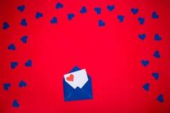 Enveloppe bleue avec la lettre d'amour au-dessus du fond rouge Images stock