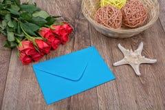 Enveloppe bleue, roses rouges et étoiles de mer sur un fond en bois Photographie stock libre de droits