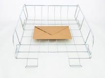 Enveloppe d'or dans la corbeille de courrier à traiter de bureau Photos stock