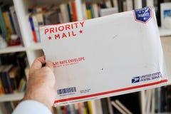 Enveloppe de colis de service postal d'USPS Etats-Unis dans des mains de l'homme Photos stock