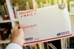 Enveloppe de colis de service postal d'USPS Etats-Unis dans des mains du ` s de l'homme Photos stock
