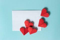 Enveloppe de livre blanc et coeurs rouges d'origami sur un fond bleu photo libre de droits