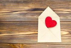 Enveloppe de papier d'emballage avec le coeur rouge en bois sur la table en bois avec Image libre de droits