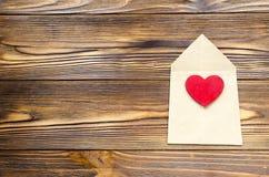 Enveloppe de papier d'emballage avec le coeur rouge en bois sur la table en bois avec Images libres de droits