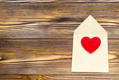 Enveloppe de papier d'emballage avec le coeur rouge en bois sur la table en bois avec Photos stock