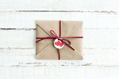 Enveloppe de Papier d'emballage avec le teg avec deux coeurs et ruban sur le dessus de table en bois blanc Images libres de droits