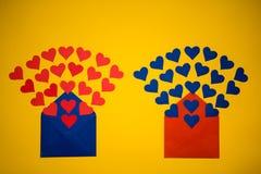 Enveloppe de salutation avec les coeurs de papier sur le fond jaune Les coeurs verse hors de l'enveloppe Les coeurs volent de l'e Image libre de droits