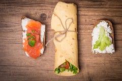 enveloppe de tortilla avec des légumes et deux sandwichs Images libres de droits