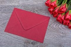 Enveloppe et roses rouges sur un fond en bois Images stock