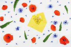 Enveloppe jaune avec des fleurs de pré et des pavots rouges, bleuets photographie stock libre de droits