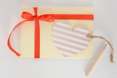 Enveloppe jaune-clair avec un ruban, une carte de coeur et un crayon rouges sur un fond blanc Photo libre de droits
