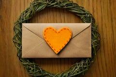 Enveloppe plate d'amour de configuration sur la table en bois avec le coeur de feutre Image libre de droits