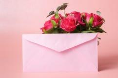 Enveloppe rose et roses rouges Photos libres de droits