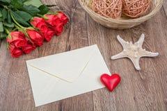 Enveloppe, roses et étoiles de mer sur un fond en bois Images libres de droits
