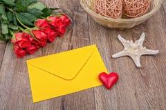 Enveloppe, roses et étoiles de mer sur un fond en bois Image stock