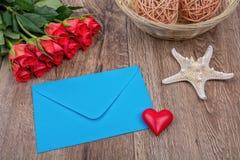 Enveloppe, roses et étoiles de mer sur un fond en bois Photo libre de droits