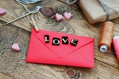 Enveloppe rouge avec l'amour de mot, les formes de coeur, l'aiguille et le fil Photographie stock libre de droits