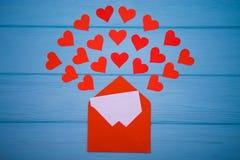Enveloppe rouge avec la lettre d'amour au-dessus du fond bleu avec beaucoup de coeurs autour Images stock