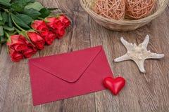 Enveloppe rouge, roses rouges et étoiles de mer sur un fond en bois Image stock