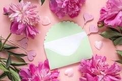 Enveloppe verte avec des pivoines et des coeurs décoratifs sur un CCB rose Images stock