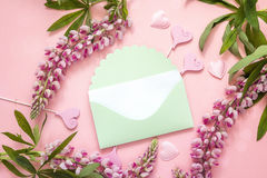 Enveloppe verte avec la fleur de loup et coeurs décoratifs sur une goupille Images libres de droits