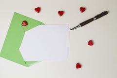 Enveloppe verte, message, stylo et petits coeurs rouges sur la table blanche Lettre d'amour, concept de jour de valentines Photos stock