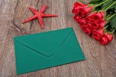 Enveloppe verte, roses rouges et étoiles de mer sur un fond en bois Photographie stock libre de droits