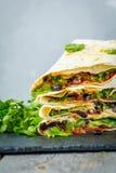 Enveloppes végétariennes de burritos avec les haricots, l'avocat et le fromage sur une ardoise Image libre de droits