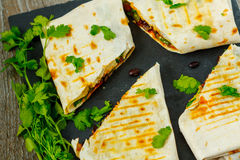 Enveloppes végétariennes de burritos avec les haricots, l'avocat et le fromage sur une ardoise Image stock