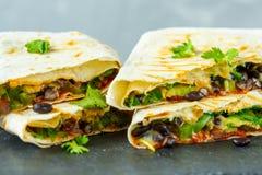 Enveloppes végétariennes de burritos avec les haricots, l'avocat et le fromage sur une ardoise Images libres de droits