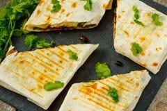 Enveloppes végétariennes de burritos avec les haricots, l'avocat et le fromage sur une ardoise Photographie stock