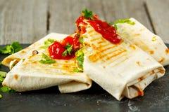 Enveloppes végétariennes de burritos avec les haricots, l'avocat et le fromage sur une ardoise Photo libre de droits
