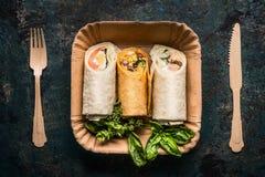 Enveloppes végétariennes de tortilla dans la plaque à papier et les couverts en bois sur le fond foncé, vue supérieure, fin  Cass photo libre de droits