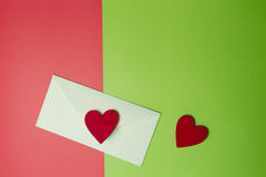 Enveloppez avec deux coeurs sur le fond de verdure et de papier coloré de rouge Vue supérieure Copiez l'espace pour le texte Image libre de droits