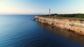 Envergure du bourdon le long des falaises sur le bord de la mer donnant sur le phare pendant l'été au coucher du soleil clips vidéos