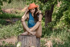 Enviable young woman sits on a stump the backdrop of the garden. A Curly girl touching her cowboy hat Stock Photos