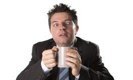 Envicie al hombre de negocios en traje y ate sostener la taza de café como maniaco en el apego del cafeína foto de archivo
