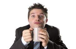 Envicie al hombre de negocios en traje y ate sostener la taza de café como maniaco en el apego del cafeína imagen de archivo libre de regalías