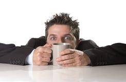 Envicie al hombre de negocios en traje y ate sostener la taza de café como maniaco en el apego del cafeína fotografía de archivo libre de regalías