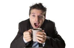 Envicie al hombre de negocios en traje y ate sostener la taza de café como maniaco en el apego del cafeína fotografía de archivo
