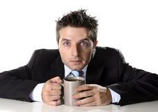 Envicie al hombre de negocios que sostiene la taza de café ansiosa y loca en el apego del cafeína imágenes de archivo libres de regalías