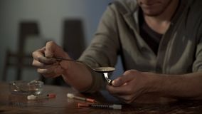 Envicie la preparación de la dosis de la droga para la inyección, calentando la heroína en la cuchara, cierre para arriba imagen de archivo