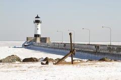 Envie a âncora na costa ao longo do cais com o farol em Duluth, Minne fotos de stock