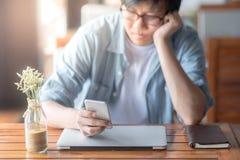 Envio de mensagem de texto asiático novo do homem no smartphone no café fotos de stock