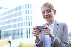 Envio de mensagem de texto da mulher de negócios através do telefone esperto fora Fotos de Stock Royalty Free
