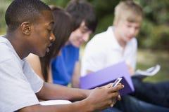 Envio de mensagem de texto do estudante universitário Imagens de Stock