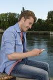 Envio de mensagem de texto feliz do homem novo Foto de Stock