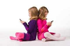 Envio de mensagem de texto gêmeo bonito das meninas Imagens de Stock