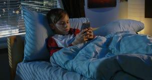 Envio de mensagem de texto do menino ao encontrar-se na cama video estoque